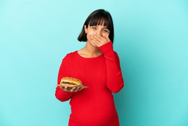 Jonge zwangere vrouw die een hamburger over geïsoleerde achtergrond houdt gelukkig en glimlachend die mond met hand behandelt