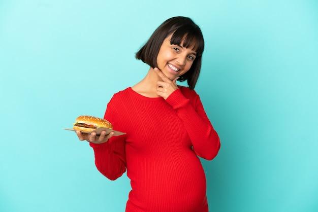 Jonge zwangere vrouw die een hamburger over geïsoleerde achtergrond houdt gelukkig en glimlachend