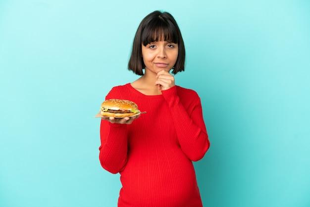 Jonge zwangere vrouw die een hamburger over het geïsoleerde denken als achtergrond houdt