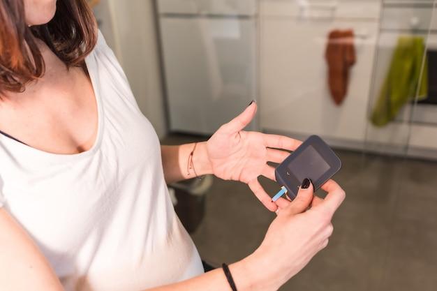 Jonge zwangere vrouw die een zelftest van de zwangerschapsdiabetes uitvoert om suiker te controleren. het meten van de bloeddruppel