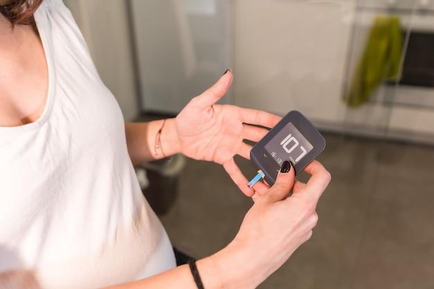 Jonge zwangere vrouw die een zelftest van de zwangerschapsdiabetes uitvoert om suiker te controleren. positief bloedtestresultaat