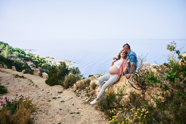 Jonge zwangere vrouw die met haar echtgenoot tegen overzeese meningen loopt