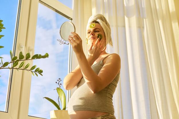 Jonge zwangere vrouw die natuurlijke zelfgemaakte fruitmaskers maakt met kiwi op gezicht, schoonheid en huidverzorging thuis. cosmetologie, dermatologie van zwangere vrouwen