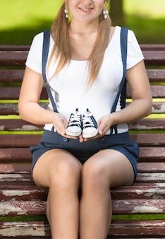 Jonge zwangere vrouw die op een bankje in het park zit en babyschoentjes vasthoudt