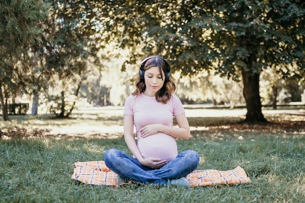 Jonge zwangere vrouw die op een lente- of zomerdag naar muziek luistert in het park