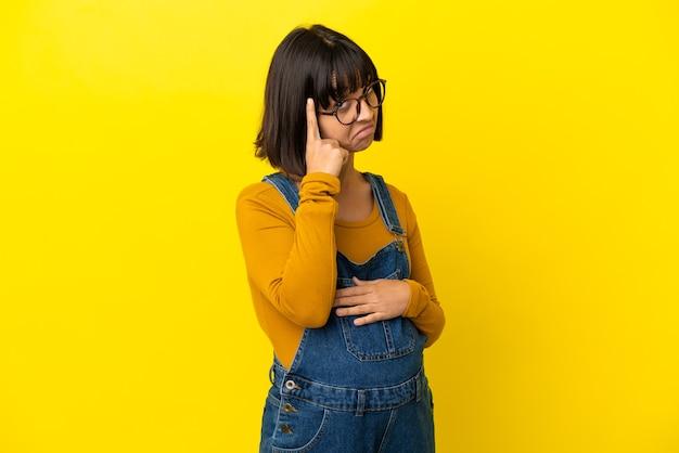 Jonge zwangere vrouw die over geïsoleerde gele achtergrond een idee denkt