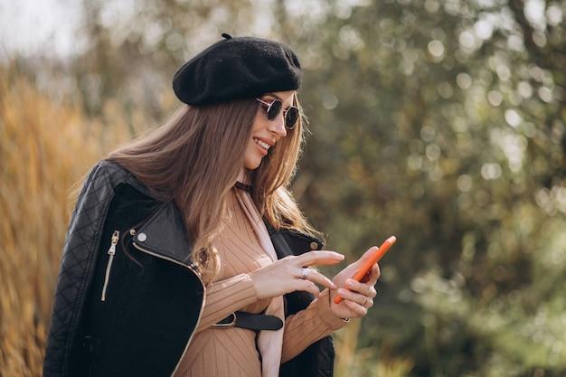 Jonge zwangere vrouw die telefoon met behulp van