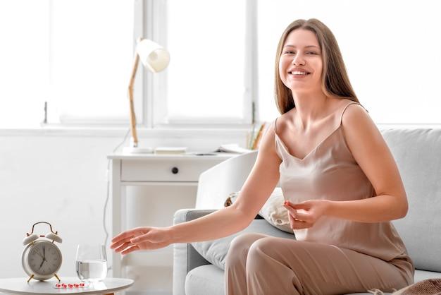Jonge zwangere vrouw die vitamines thuis neemt