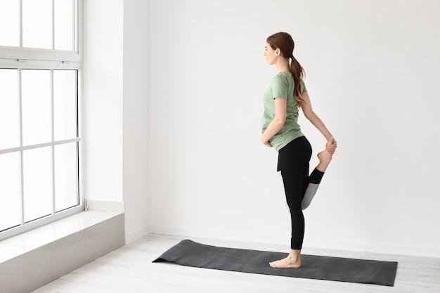 Jonge zwangere vrouw die yoga beoefent in de sportschool