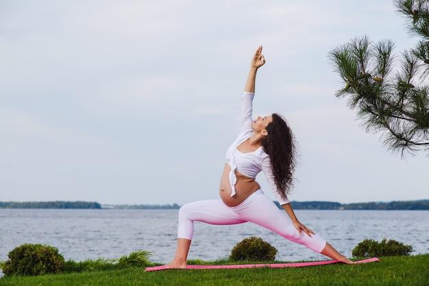 Jonge zwangere vrouw die yoga in openlucht doet