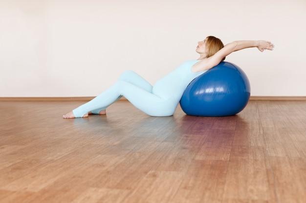 Jonge zwangere vrouw doet yoga met een fitnessbal op een lichte achtergrond