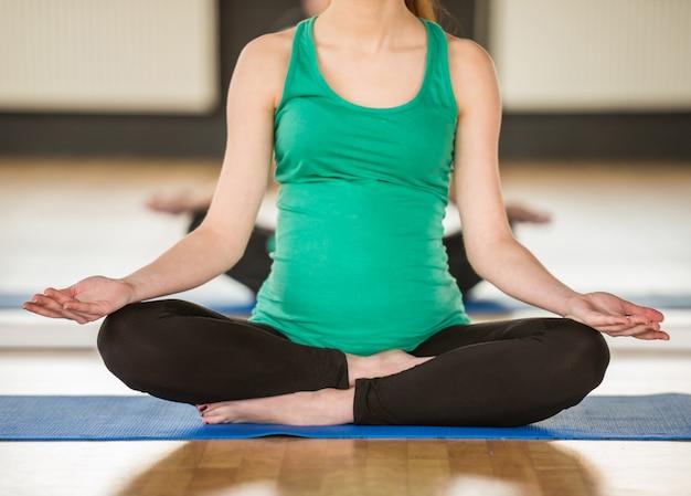 Jonge zwangere vrouw doet yoga.