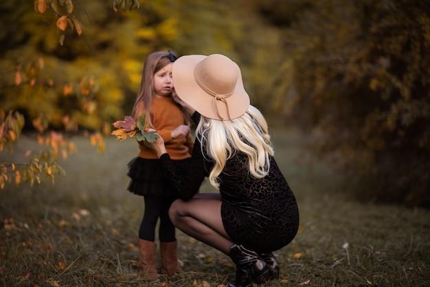 Jonge zwangere vrouw in de herfsthoed die droevig aan haar dochtertje in het park voelen