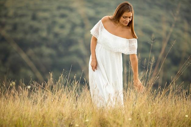 Jonge zwangere vrouw in witte jurk op het zomer-veld