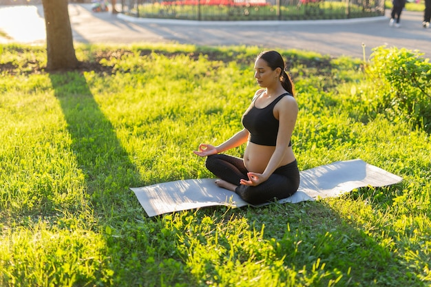 Jonge zwangere vrouw mediteren in de natuur, yoga beoefenen. zorg voor gezondheid en zwangerschap.