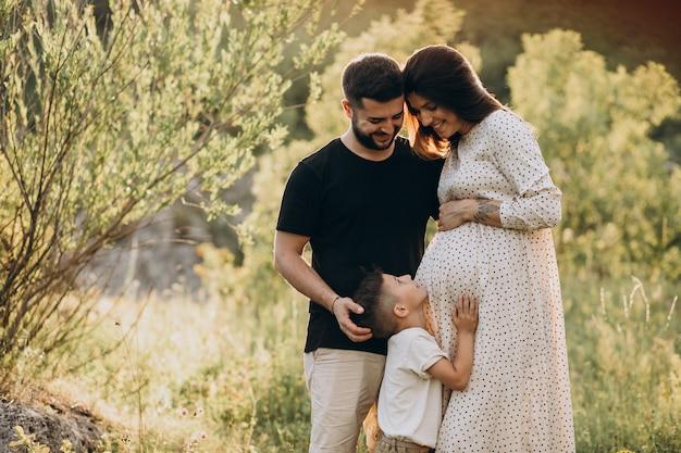Jonge zwangere vrouw met echtgenoot en zoon in een bos