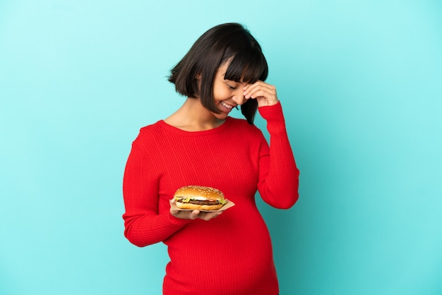 Jonge zwangere vrouw met een hamburger over geïsoleerde achtergrond lachen