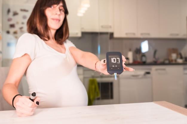 Jonge zwangere vrouw met een zwangerschapsdiabetes zelftest om suiker te controleren, met een positief resultaat