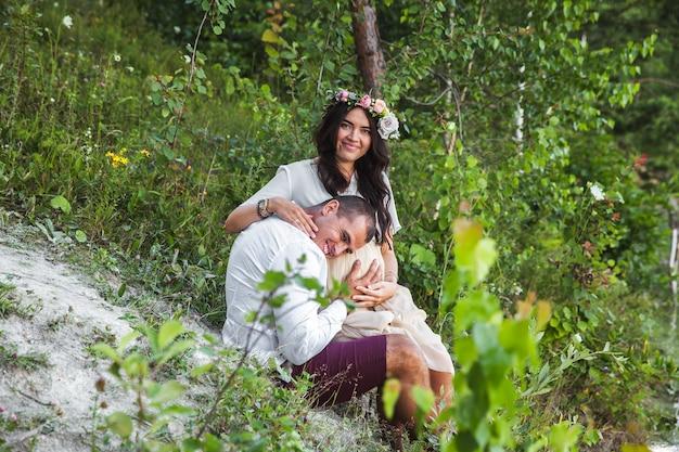 Jonge zwangere vrouw met haar echtgenoot die van de aard genieten die casual en stijljeans en wit t-shirt dragen.