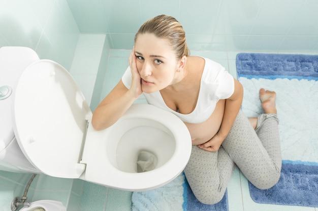 Jonge zwangere vrouw met intoxicatie zittend op de vloer bij toilet