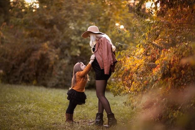 Jonge zwangere vrouw met lang blond haar in hoed spelen met haar dochtertje in het najaar park.