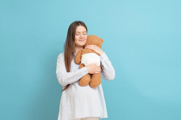 Jonge zwangere vrouw met teddybeer in handen