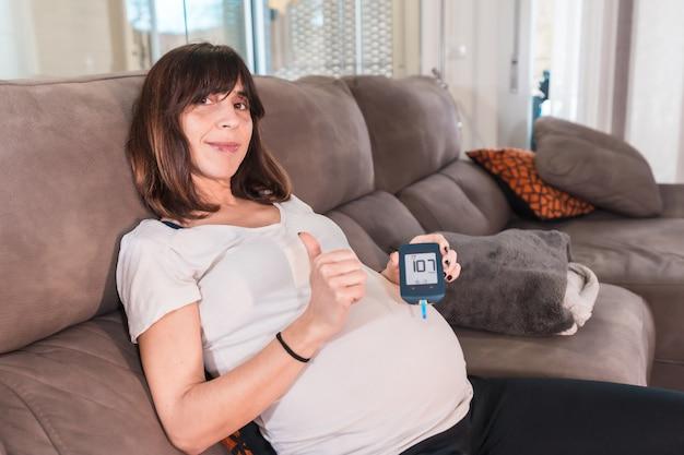 Jonge zwangere vrouw met zelftest van zwangerschapsdiabetes om suiker thuis op de bank te controleren, blij met het testresultaat