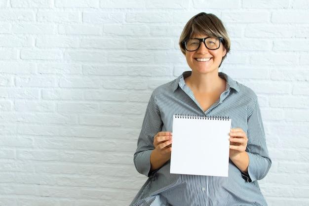 Jonge zwangere vrouw ondertekenen voor de tekst, met lege witte kaart in de buurt van buik