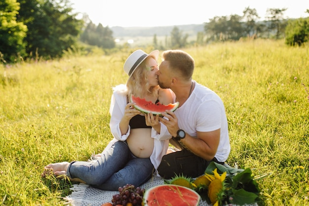 Jonge zwangere vrouw ontspannen in park buiten met haar man