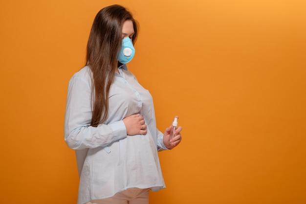 Jonge zwangere vrouw op gele muur in beschermende medische masker en spray antiseptische in de hand