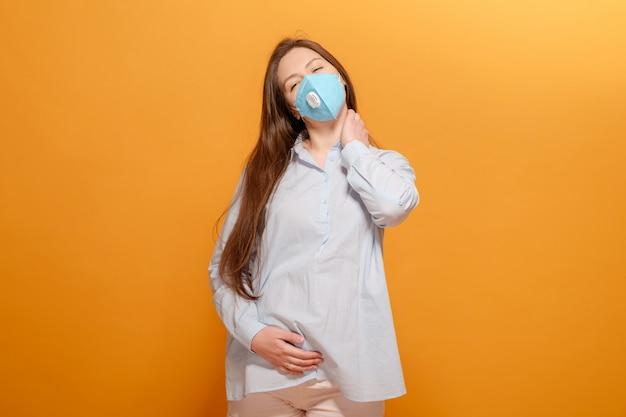 Jonge zwangere vrouw op gele muur in beschermende medische masker, pijn in de nek