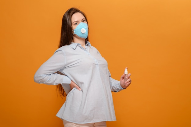 Jonge zwangere vrouw op oranje muur in beschermende medische masker en spray antiseptische in de hand