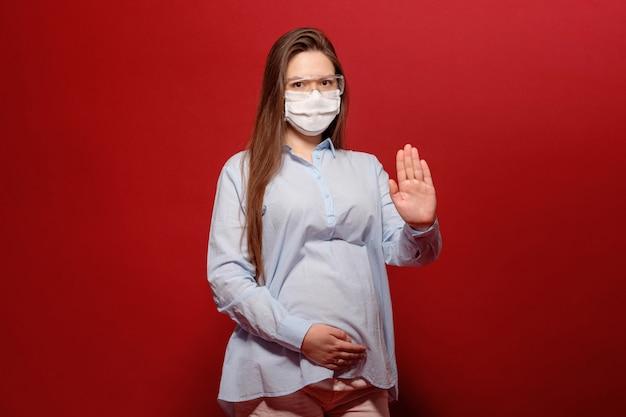 Jonge zwangere vrouw op rode muur in beschermend medisch masker houdt haar buik