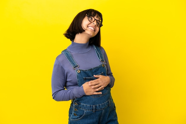 Jonge zwangere vrouw over geïsoleerde gele achtergrond die een idee denkt terwijl ze omhoog kijkt