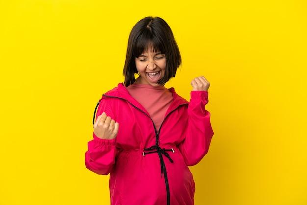 Jonge zwangere vrouw over geïsoleerde gele achtergrond die een overwinning viert