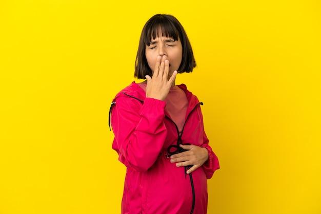 Jonge zwangere vrouw over geïsoleerde gele achtergrond die geeuwt en wijd open mond bedekt met de hand
