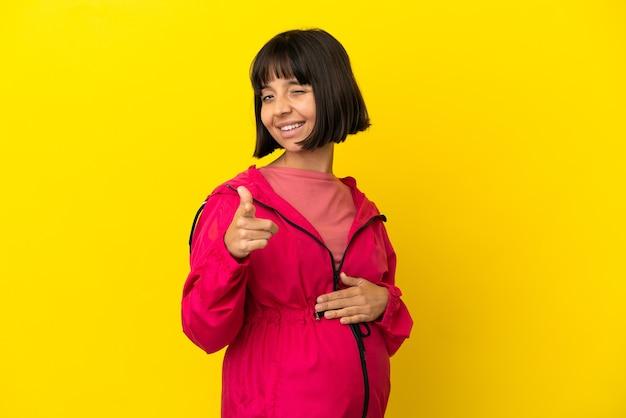 Jonge zwangere vrouw over geïsoleerde gele achtergrond die naar voren wijst en glimlacht