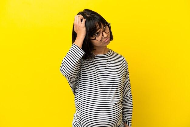 Jonge zwangere vrouw over geïsoleerde gele achtergrond die twijfelt terwijl ze aan het hoofd krabt