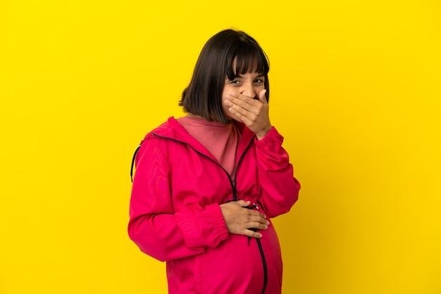 Jonge zwangere vrouw over geïsoleerde gele achtergrond gelukkig en glimlachend die mond bedekken met hand