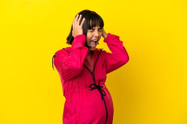 Jonge zwangere vrouw over geïsoleerde gele achtergrond gestrest overweldigd
