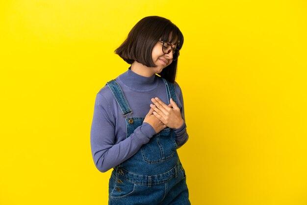Jonge zwangere vrouw over geïsoleerde gele achtergrond met pijn in het hart