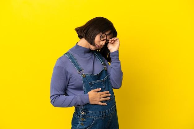 Jonge zwangere vrouw over geïsoleerde gele achtergrond met vermoeide en zieke uitdrukking