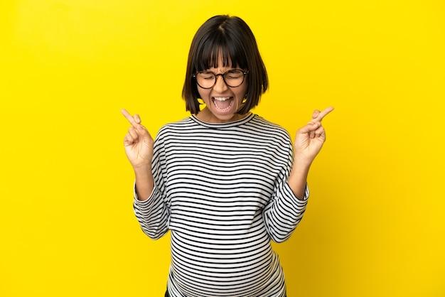 Jonge zwangere vrouw over geïsoleerde gele achtergrond met vingers over elkaar