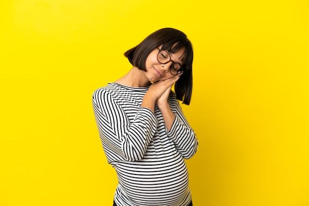 Jonge zwangere vrouw over geïsoleerde gele muur die slaapgebaar maakt in schattige uitdrukking