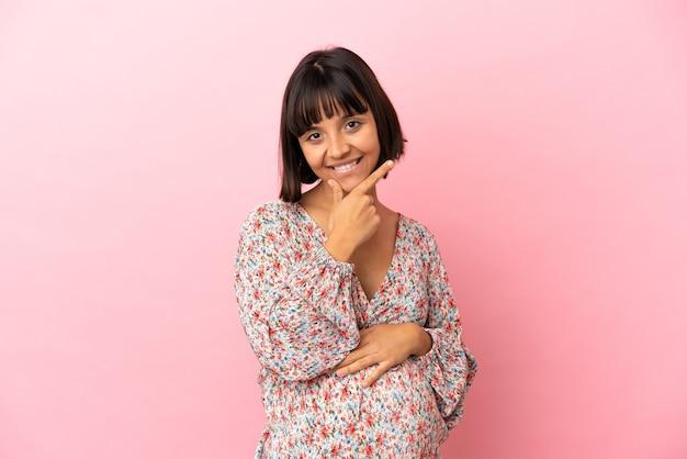 Jonge zwangere vrouw over geïsoleerde roze achtergrond gelukkig en glimlachend