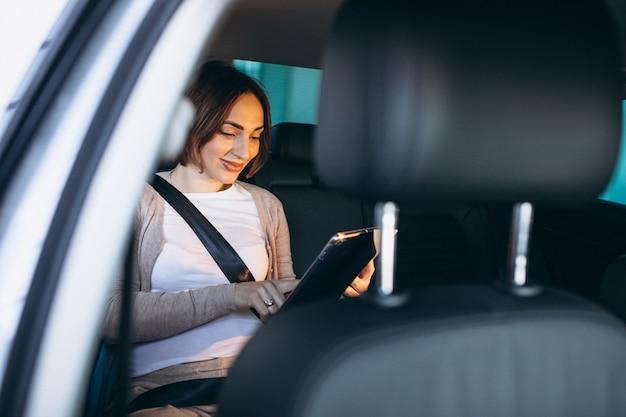 Jonge zwangere vrouw rijden in de auto naar het ziekenhuis