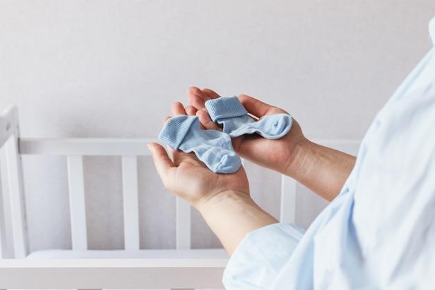 Jonge zwangere vrouw staat in de buurt van babywieg met een paar blauwe sokken voor pasgeborenen in verwachting