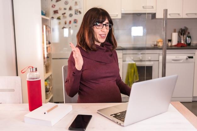 Jonge zwangere vrouw telewerken met de computer vanuit huis vanwege de moeilijkheden bij het werken, een videogesprek voeren