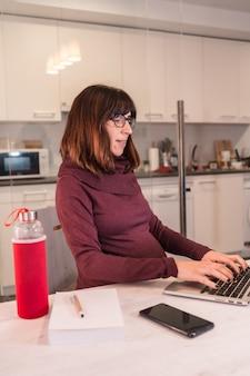 Jonge zwangere vrouw telewerken met de computer vanuit huis vanwege de moeilijkheden bij het werken