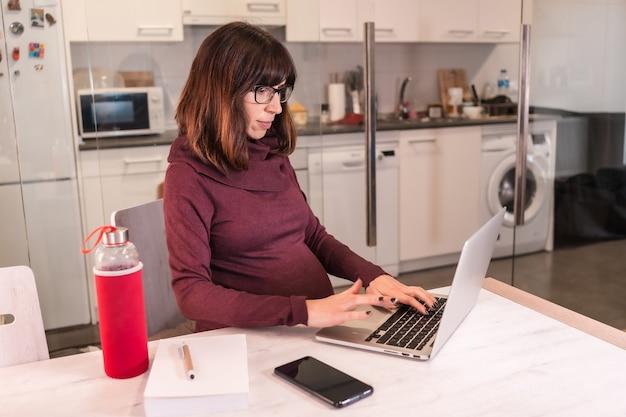 Jonge zwangere vrouw telewerken vanuit huis vanwege de moeilijkheden bij het werken